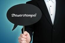 Steuerstempel. Mann (Anwalt) Hält Schild Mit Beschriftung. Sprechblase Mit Text (deutsch). Hintergrund Blau