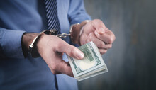 Caucasian Businessman In Handcuffs And Money. Corruption