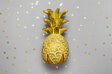 Trendy Colors Of The Year 2021. Illuminating And Ultimate Gray. Wooden Yellow Pineapple With Confetti Stars On Gray Background Flat Lay Top View. Creative Mockup With Painted Pineapple. Summer Concept