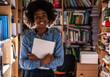 Leinwandbild Motiv Portrait of young black female student .She standing in college library.