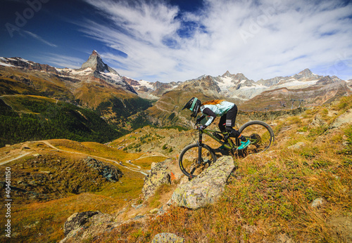 Women on a mountainbike drives down the wallis mountains for the matterhorn in the swiss alps #404611150