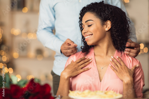 Fotografija Young black guy wearing necklace on his happy woman