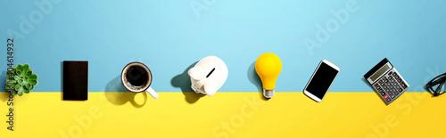 Obraz na plátně Office supplies with a piggy bank and a lightbulb - flat lay