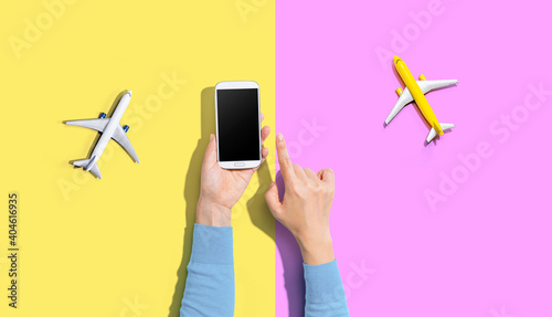 Fotografie, Obraz Person holding a smart phone with airplanes from above