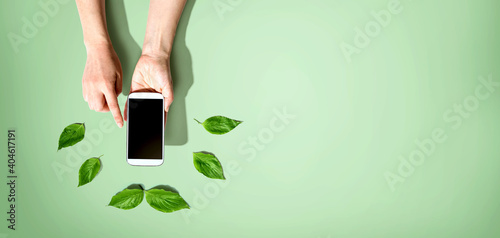 Fotografie, Obraz Person holding a smartphone with green leaves