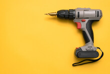 Screwdriver Drill With Step Conical Drill Bit On The Yellow Flat Lay Background With Copy Space.