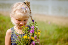 Cute Child  With Huge Colorful Bunch Of Wild Flowers