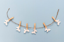 White Wooden Butterflies Pinned To A Rope With Clothespins On A Light Blue Background.