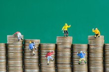 Close-up Of Figurines On Coins Stack Against Green Background