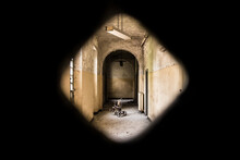 Tricycle In Corridor Seen Through Key Hole In Abandoned Building