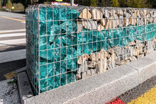 Close-up Detail Of New Modern Beautiful Gabion Fence With Metal Cage Filled By Crushed Stone And Shattered Artificial Blue Glass Rocks. City Street Road Pavement Protection