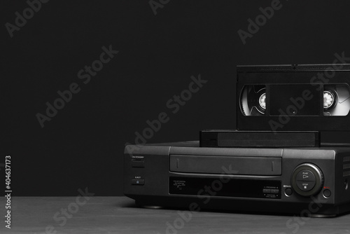 Video recorder and video tapes on the table on the black background Fototapet