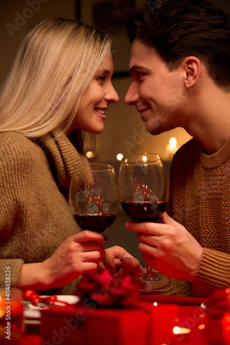 Obraz Happy young couple in love bonding, holding glasses, drinking wine, enjoy tender moment together celebrating Valentines day having romantic dinner date with candles sit at home table or in restaurant. - fototapety do salonu