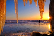 Close-up Of Icicles Against Beach During Sunset