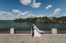 Smiling Newlyweds Hug, Standing On The Alley In The City, Against The Background Of The River, Sky And Landscape. Wedding Portrait Of A Groom In A Suit And A Beautiful Bride With A Long Veil.