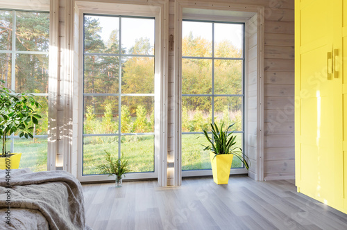 Obraz Bright interior, room in wooden house with large window. Scandinavian style. The trendy colors of 2021 are gray and yellow - fototapety do salonu