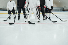 Low Section Of Several Hockey Players And Their Trainer With Sticks On Ice Rink