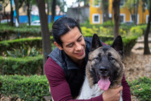 Young Hispanic Man Petting And Holding His American Akita Dog In The Park