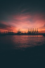 Silhouette Cranes By Sea During Sunset