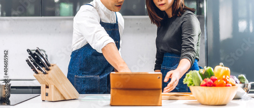 Papel de parede Young asian family couple having fun cooking together with fresh vegetable salad on table