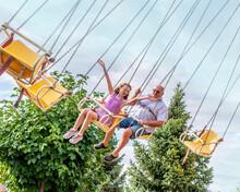 Teen Child And Grandpa Enjoying A Carnival Ride