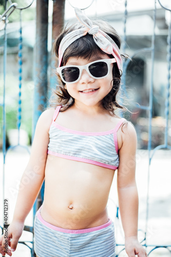 Obraz Portrait Of Cute Girl In Swimwear Wearing Sunglasses While Standing Against Gate - fototapety do salonu