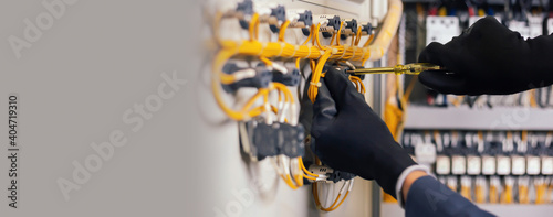 Obraz Electrician engineer work tester measuring voltage and current of power electric line in electical cabinet control.and wires on relay protection system. Bay control unit. Medium voltage switchgear. - fototapety do salonu