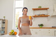 Leinwandbild Motiv Happy young fitness woman athete in sportswear standing and drinking fresh orange juice from glass before or after workout at home. Active healthy lifestyle, clean eating concept