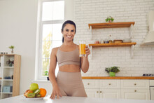 Happy Young Fitness Woman Athete In Sportswear Standing And Drinking Fresh Orange Juice From Glass Before Or After Workout At Home. Active Healthy Lifestyle, Clean Eating Concept
