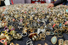A Selection Of Rings, Pendants And Jewelry On A Table Covered In Black Fabric