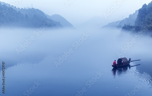 Obraz na plátně Man Rowing Boat In Lake Against Sky During Foggy Weather