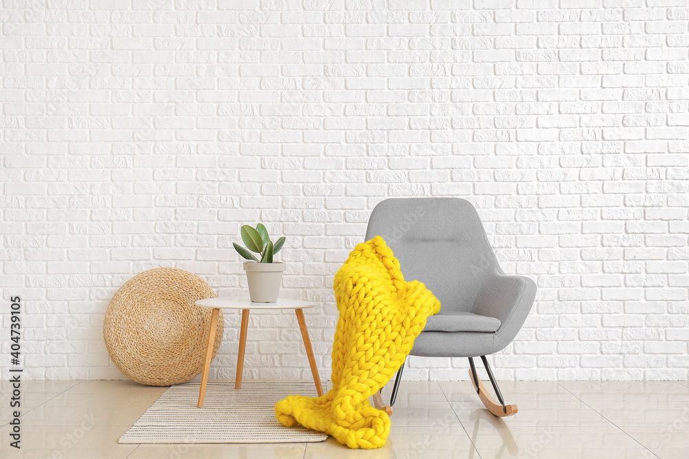 Fototapeta Interior of modern room with armchair and knitted plaid