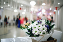 A Bouquet Of Daisies With Blue Flowers Close-up In A Supermarket With A Blurry Background