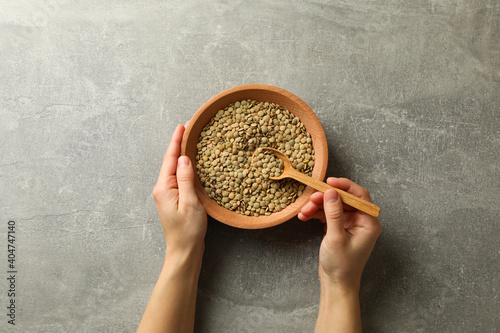 Woman hands hold bowl and spoon with legumes on gray background