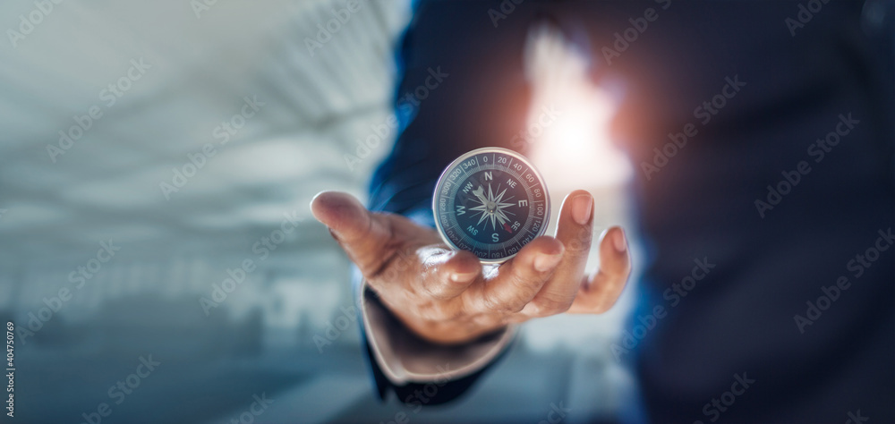 Fototapeta Businessman hand holding compass navigating business direction and successful strategic solution.Reflect accomplishment in terms of research and development growth market and financial profitability.
