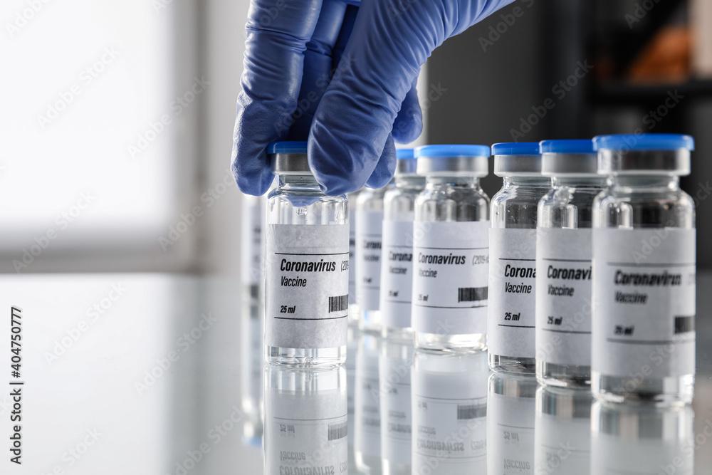 Fototapeta Doctor taking vaccine for immunization against COVID-19 from table