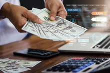 Banking And Finance Accounting, Businessman Holding Banknote And Analyzing Data Growth Graph On Mobile And Laptop And Using Calculator To Calculate The Numbers Currency Exchange.