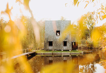 Wooden Whimsical Cozy House In The Autumn Park Near The Lake And A Couple In Love