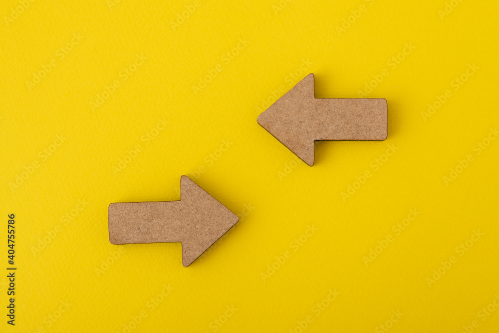Fototapeta Two wooden arrows on yellow background. Direction signs. Copy space. Mock up