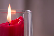 Close-up Of Lit Candle Against Gray Wall