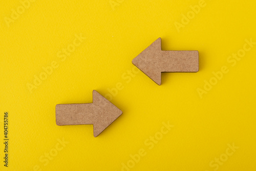 Obraz Two wooden arrows on yellow background. Direction signs. Copy space. Mock up - fototapety do salonu