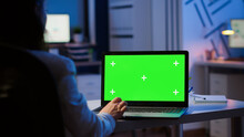 Woman Looking At Laptop With Green Mockup During Night Time In Start Up Business Office Working Overtime. Freelancer Watching Desktop Monitor Display With Green Screen, Chroma Key, Typing Writting