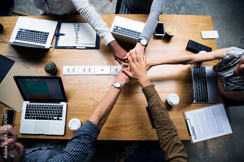 High Angle View Of Business Team Stacking Hands At Desk In Office