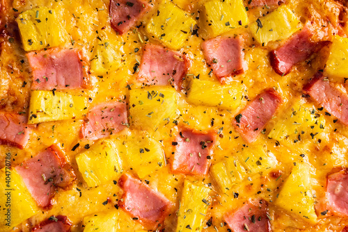 Just baked hawaiian pizza with freshly chopped pineapple and ham on the rustic wooden background. Selective focus.