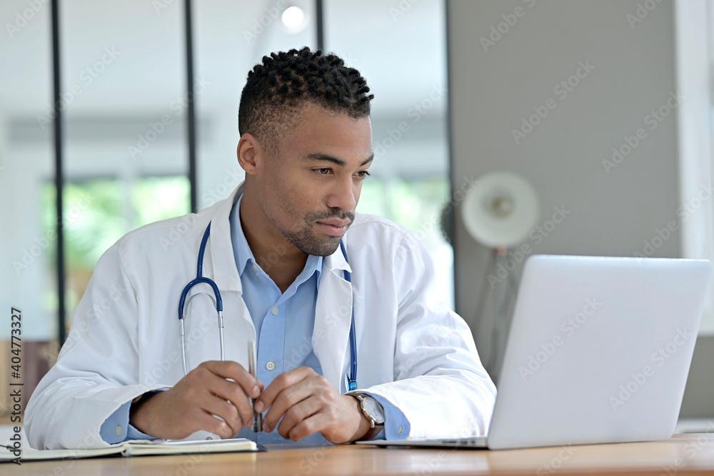 Fototapeta Portrait of general practitioner working in office in laptop