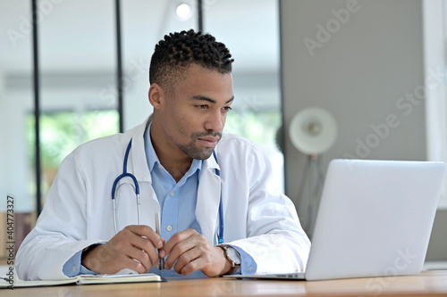 Portrait of general practitioner working in office in laptop Fotobehang