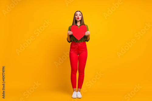 Fototapeta premium Full length body size view of nice straight-haired girl holding in hands heart sending air kiss isolated on bright yellow color background