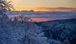 Farbenprächtiger Wintermorgenhimmel über verschneiten Wäldern, Panoramaformat mit viel Textfreiraum