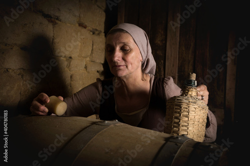 Opening barrel in medieval wine cellar