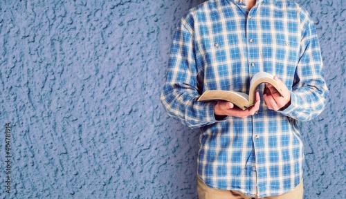 Obraz na plátně Man reading old heavy book on background